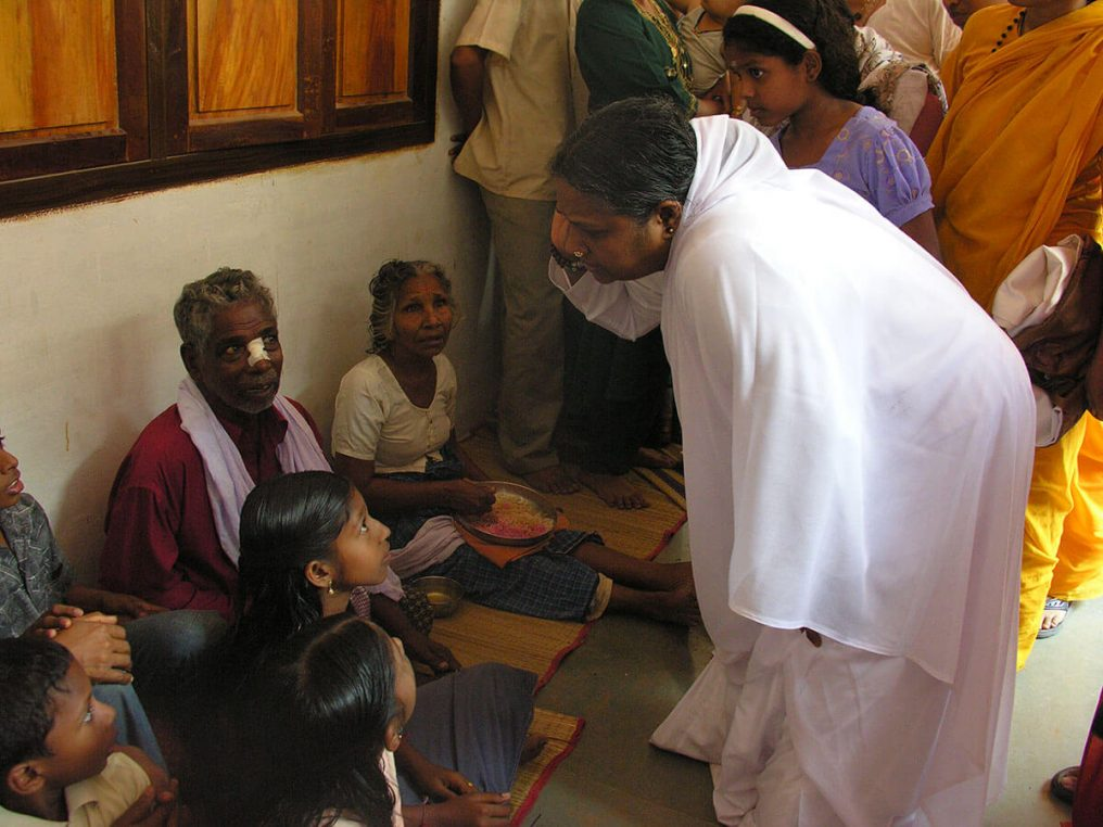 Amma consoling the suffering after the Tsunami