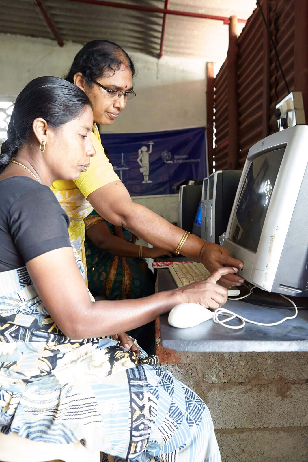 A women instructing another woman on the computer